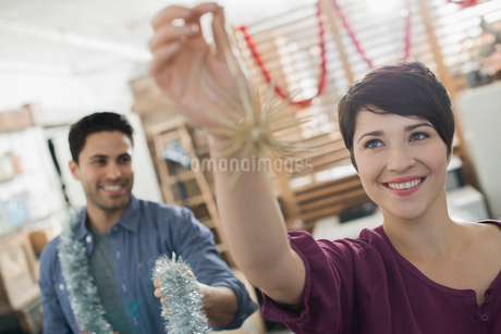 Christmas decorations. A man and woman holding tinsel and decorations.の写真素材 [FYI02251666]