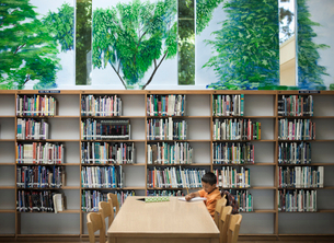 A child seated at a library table working, studying his books.の写真素材 [FYI02251675]