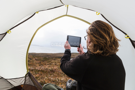 A man sitting in the shelter of a tent looking out, taking a photograph with a digital tabletの写真素材 [FYI02251680]