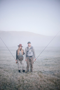 Two people walking across a meadow in early morning mist carrying fishing rods.の写真素材 [FYI02251686]