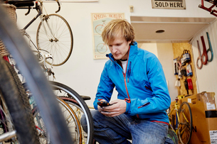 A young man using his smart phone in a cycle shop, making a call.の写真素材 [FYI02251687]