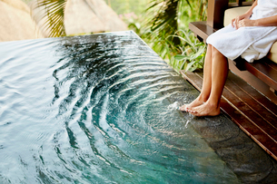 A person sitting on a bench with her feet in the shallow water of a pool, making ripples.の写真素材 [FYI02251705]
