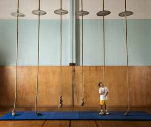 A child standing at the base of a climbing rope looking upwards.の写真素材 [FYI02251712]