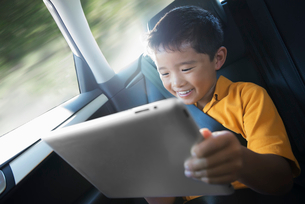 A boy travelling in the back seat of a car using a digital tablet.の写真素材 [FYI02251713]