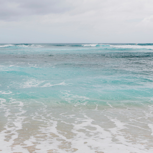 Turquoise ocean water, waves on the beach and an overcast sky.の写真素材 [FYI02251715]