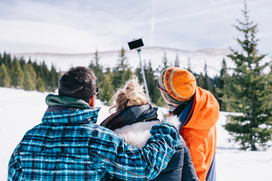 Three people, two men and a young woman in skiing gear posing for a selfie, one holding a selfie stiの写真素材 [FYI02251716]