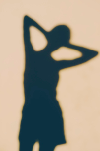 The outline of a human body, a shadow against a plain background, a female shape.の写真素材 [FYI02251717]