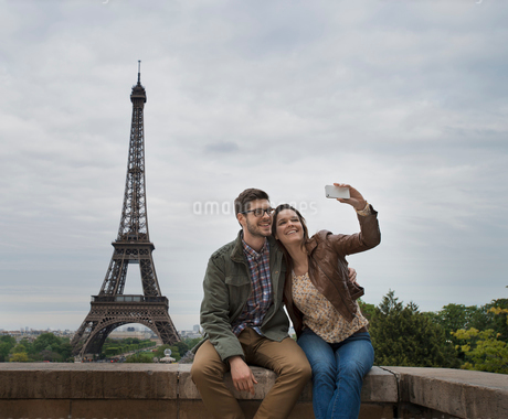 A couple seated side by side taking a selfy with the Eiffel Tower in the background.の写真素材 [FYI02251725]