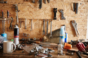A workbench and tool board in a cycle repair shop. Coffee mug, hand tools, nuts and bolts and spanneの写真素材 [FYI02251732]