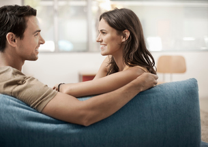 A young couple sitting on a sofa, gazing at each other, a man and woman, boyfriend and girlfriend.の写真素材 [FYI02251740]