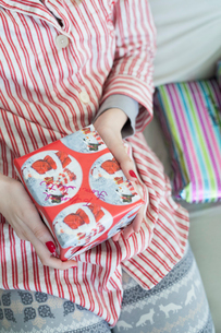 A girl holding a small wrapped Christmas present.の写真素材 [FYI02251747]
