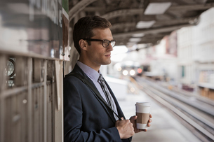 A working day. Businessman in a work suit and tie holding a cup of coffee on a railway platform.の写真素材 [FYI02251748]