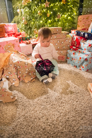 A baby girl sitting among piles of wrapped presents around the Christmas tree on Christmas Day.の写真素材 [FYI02251760]