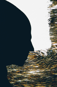 Shadow of a man's head, in profile, against a painted wall.の写真素材 [FYI02251765]