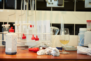 A winery laboratory. A worktop with flasks and tubes, a glass of wine and a screwdriver.の写真素材 [FYI02251771]