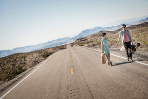 A young couple, man and woman walking hand in hand on a tarmac road in the desert carrying cases.の写真素材 [FYI02251772]