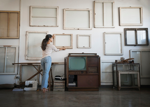 Loft decor. A woman hanging picture frames, blank canvases on a wall.の写真素材 [FYI02251783]