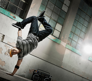A young man breakdancing on the street of a city, doing a one handed handstand.の写真素材 [FYI02251792]