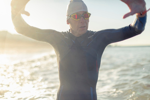 A swimmer in a wet suit, swimming hat and goggles, by the water's edge.の写真素材 [FYI02251808]