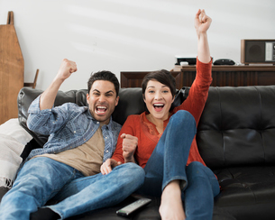 A man and woman sitting on a sofa, celebrating and pumping the air with their fists. Watching sportの写真素材 [FYI02251827]