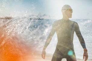 A swimmer in a wet suit standing by the water's edge.の写真素材 [FYI02251831]