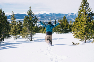 A man running through deep snow on a mountainside.の写真素材 [FYI02251833]