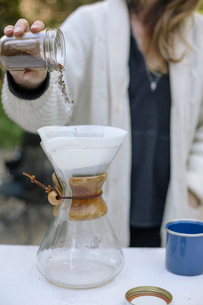 Woman pouring ground coffee from a jar into a glass coffee maker.の写真素材 [FYI02251846]