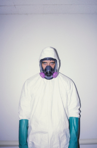 A man wearing a white protective clean suit and long thick blue gloves, and breathing mask.の写真素材 [FYI02251852]
