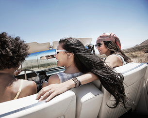 Three young people in a pale blue convertible car, driving on the open road across a flat dry plain,の写真素材 [FYI02251863]
