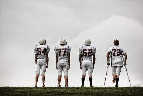 A group of football players, young people in sports uniform and protective helmets. One person usingの写真素材 [FYI02251875]