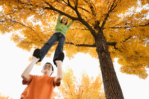 A girl hanging by her arms from a tree branch in autumn, and a boy holding her ankles.の写真素材 [FYI02251884]