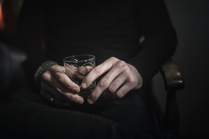 A man's hands holding a glass of whisky.の写真素材 [FYI02251900]