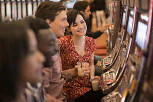 A group of people playing the slot machines in a casino.の写真素材 [FYI02251911]