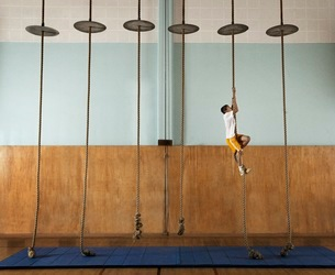 A child climbing up a rope in a school gym.の写真素材 [FYI02251918]