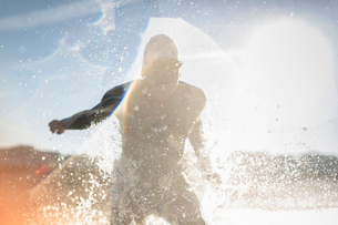 A swimmer in a wet suit running into the water, making a splash.の写真素材 [FYI02251923]