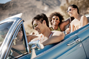 A group of friends in a pale blue convertible on the open road, driving across a dry flat plain surrの写真素材 [FYI02251924]