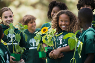 Children in a group learning about plants and flowers, carrying plants and sunflowers.の写真素材 [FYI02251927]