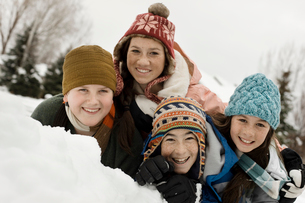 Winter snow. Four children grouped laughing by a snow bank.の写真素材 [FYI02251932]