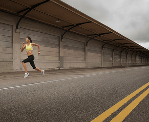 A woman running along an urban road, arms working and legs striding out.の写真素材 [FYI02251933]