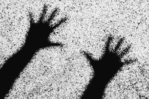 Shadow of two human hands with outstretched fingers on a wall.の写真素材 [FYI02251943]