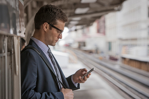 A working day. Businessman in a work suit and tie on a station platform, checking his phone,の写真素材 [FYI02251949]