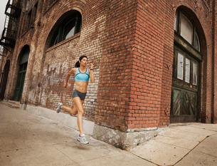 A woman running along an urban road, jogging, stretching her arms and legs.の写真素材 [FYI02251951]