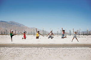 A row of six young people leaping in the air, arms outstretched in wide open space in the desert.の写真素材 [FYI02251953]