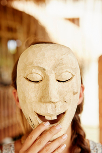 A person holding up a wooden mask on front of her face.の写真素材 [FYI02251977]