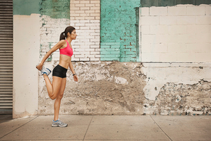 A woman in running gear, crop top and shorts, stretching her body and preparing for a run, or coolinの写真素材 [FYI02251989]