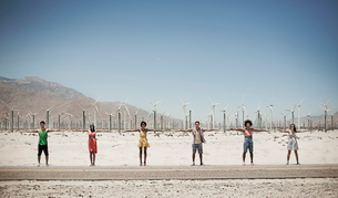 A row of six young people standing arms outstretched by the roadside with a backdrop of wind turbineの写真素材 [FYI02251998]