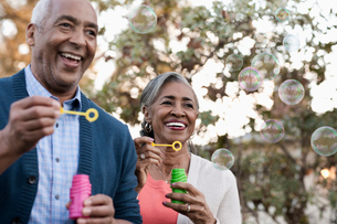 A mature couple, man and woman blowing bubbles celebrating an occasion outdoors.の写真素材 [FYI02252002]