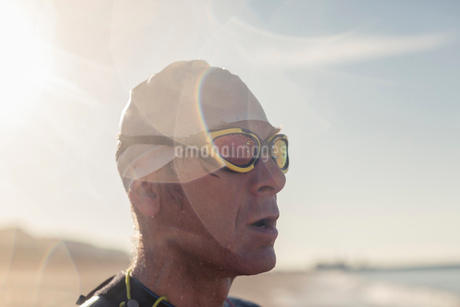 A swimmer in a wet suit, swimming hat and goggles on a beach.の写真素材 [FYI02252003]