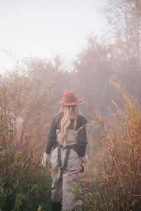 A woman in a hat and warm clothes, carrying a fishing rod.の写真素材 [FYI02252018]