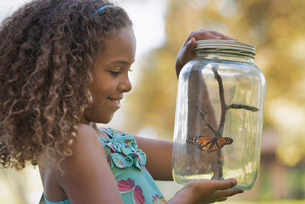 A girl holding a glass jar with a butterfly inside it.の写真素材 [FYI02252019]